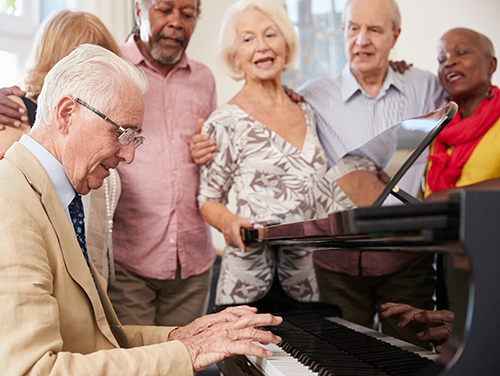 A group of senior citizens around a piano.