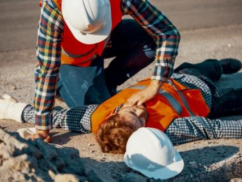 worker in hard hat checking vital signs of injured co-worker