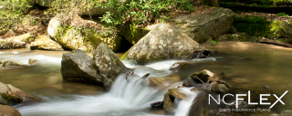 Photo of rushing water falling over rocks in a creek