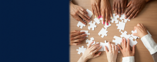 Photo of hands of diverse group around a table assembling puzzle