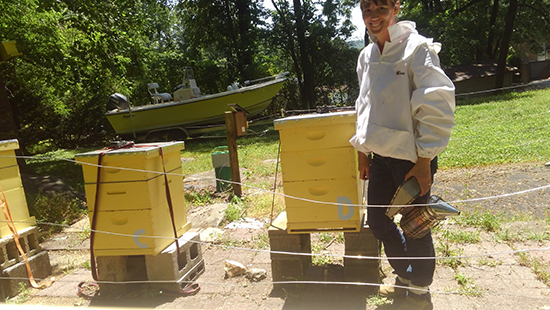 Laura Shields posing in front of her bee hives in her yard. Photo courtesy of Laura Shields.