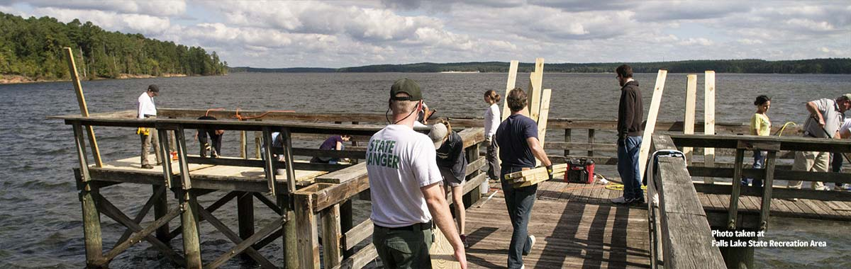 Friends working on the pier at Falls Lake State Recreation Area