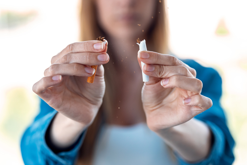 Woman breaking cigarette in half