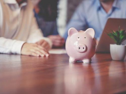 Two people looking at computer in the background, with a piggy bank in the foreground