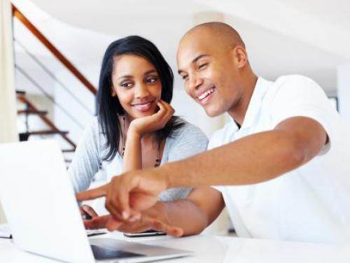 Smiling couple looking at laptop computer