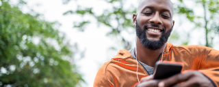 Young man looking down at his phone smiling