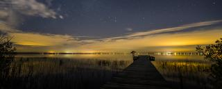 Milky Way is faintly visible in the dark sky over Lake Waccamaw