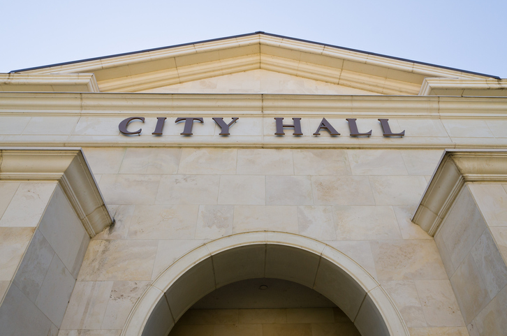 "Photo of the front of a building with the words ""City Hall"" on it"