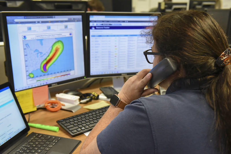 Operator on phone with computer screen showing approaching hurricane in rain and wind totals expected