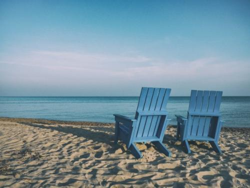 Two blue Adirondack chairs sitting on a beach