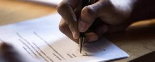 Person's hand filling out a form