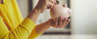 Person putting quarter into piggy bank.