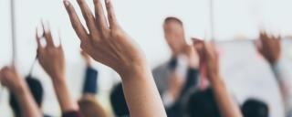 People in a meeting raising their hands with questions of the presenter at the front of the room.