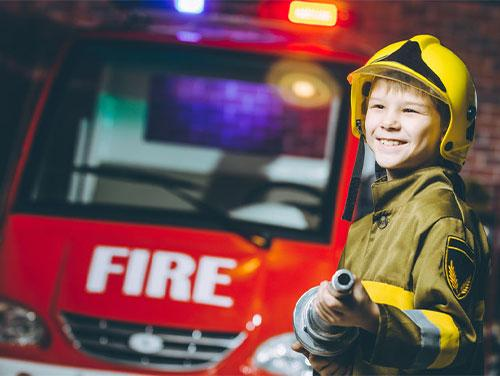 Child with turnout gear and hose