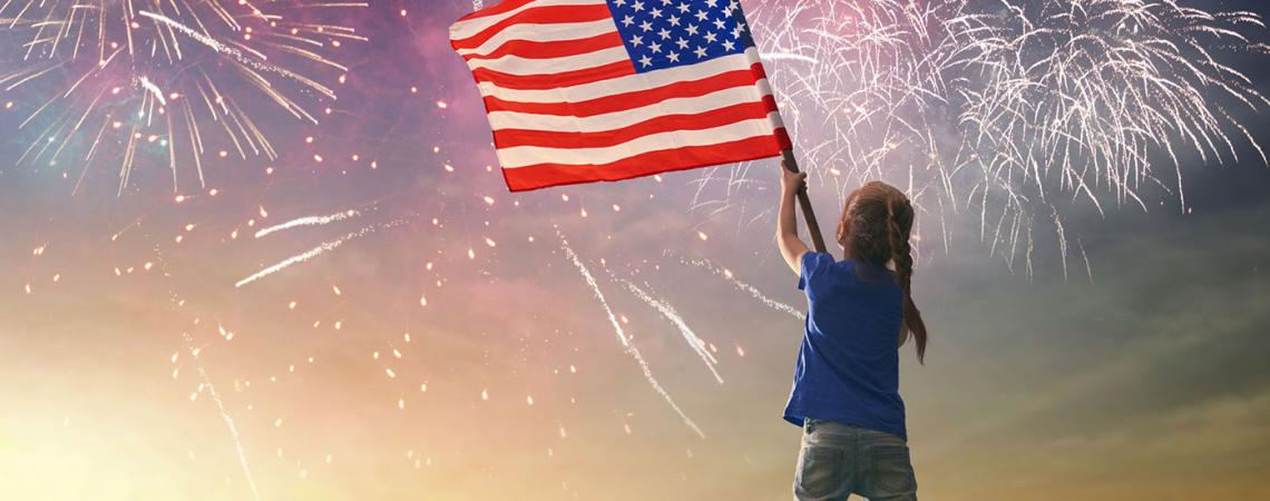 Girl waiving American flag at fireworks show