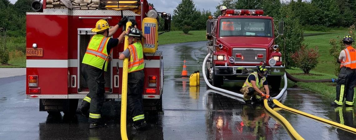 Firefighters, hoses and fire trucks