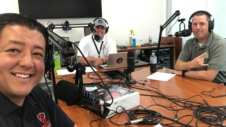 Three OSFM employees, recording a podcast with Microphones in front of them.