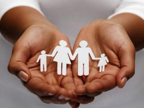 hands holding paper dolls of family