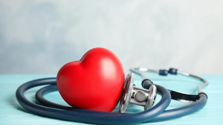 plastic red heart surrounded by stethoscope