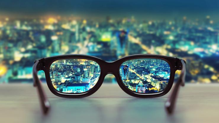 pair of eyeglasses on window ledge with city lights in background