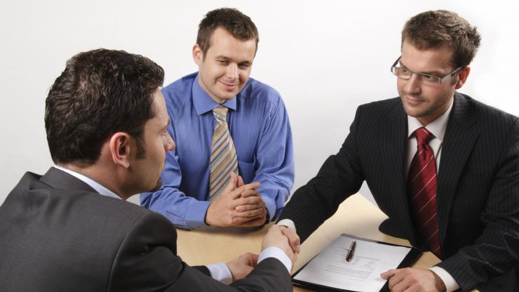 young men sitting at table shaking hands