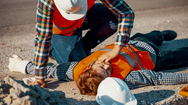 worker in hard hat checks vital signs of injured co-worker