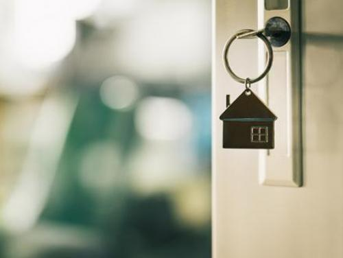 Key in the lock of a front door with a house-shaped keychain