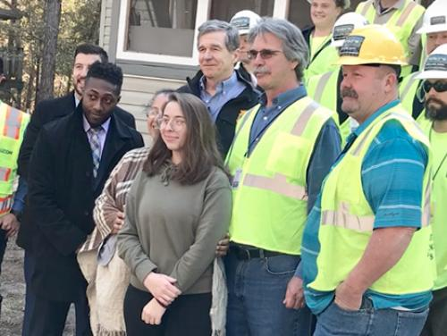 Group of people posing for photo with construction crew