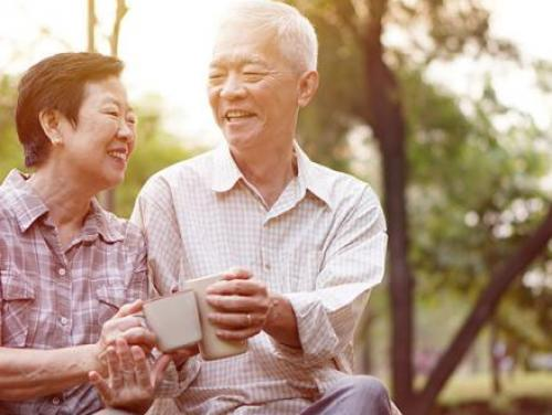Older Asian couple drinking coffee outside