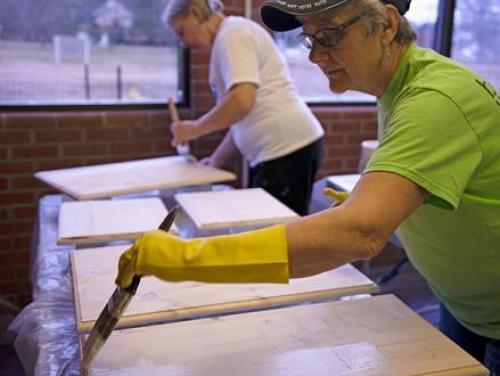 Two volunteers painting planks of wood
