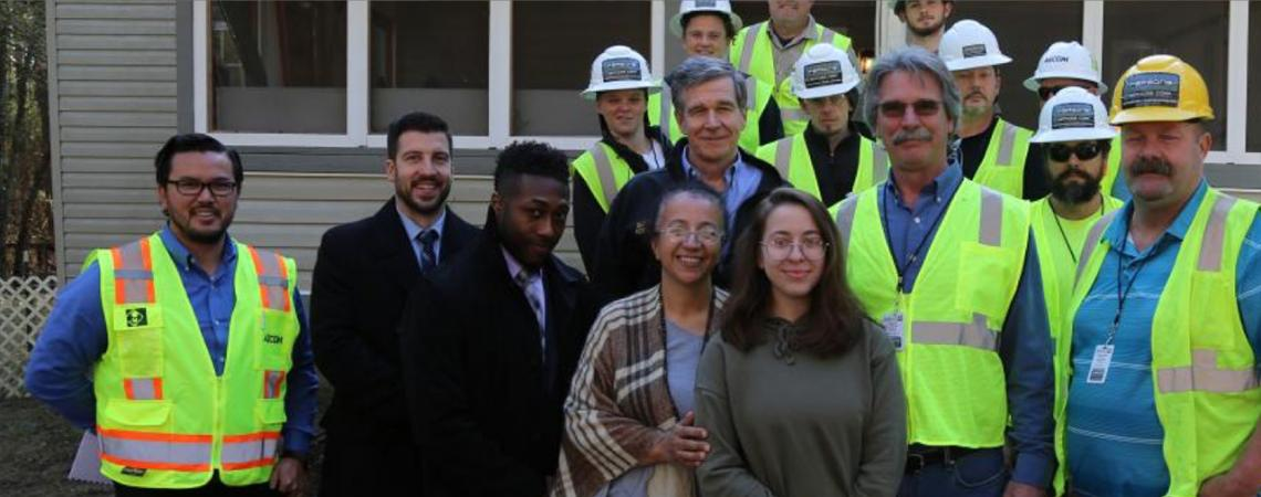 Governer Roy Cooper with family of Sandra Settle and construction team