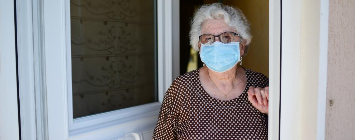 senior woman opening door with face mask on