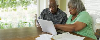 Older African American couple looking at computer
