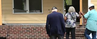 Elderly couple being guided into home