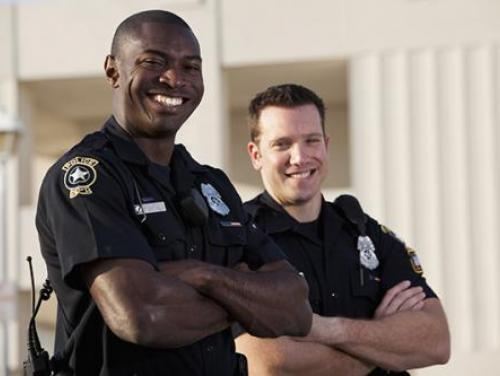 Two police officers standing side by side smiling at the camera