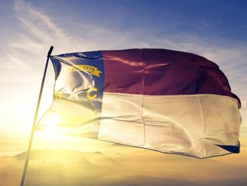 State of North Carolina Flag with sun behind it