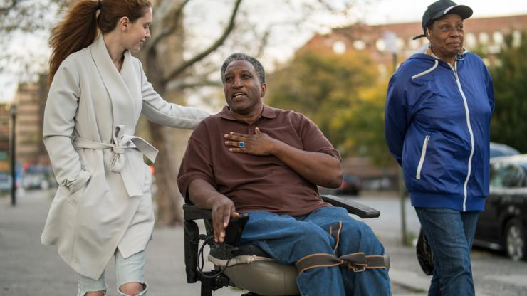 Man in a wheelchair out with an aide and a family member