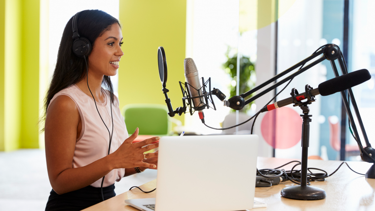 Lady recording a podcast at a microphone