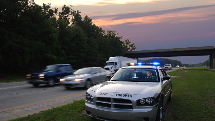 North Carolina State Highway Patrol officer in his car beside the road