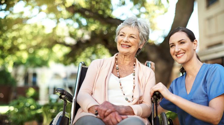 Woman in wheelchair enjoying the outdoors with an aide
