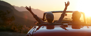 Two senior citizens in car watching sunset