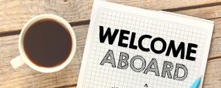 """Cup of coffee sitting beside a """"Welcome Aboard"""" booklet on a table"""