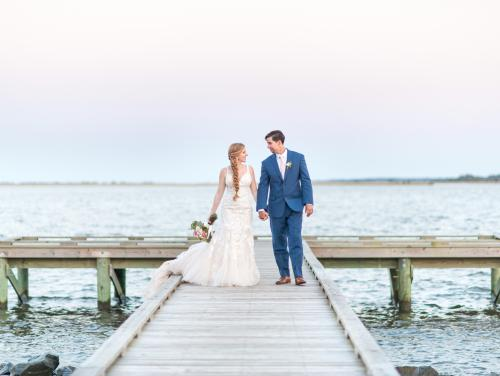 Bride and groom walking on pier at Roanoke Island Festival Park wedding