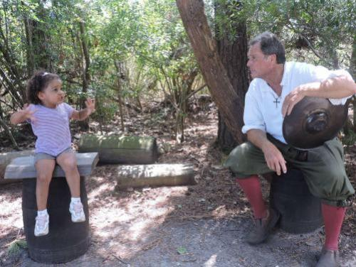 Toddler talking to a historic interpreter in the Settlement Site at Roanoke Island Festival Park
