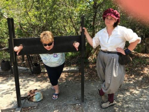 Women trying out the pillory with a historic interpreter in the Settlement Site at Roanoke Island Festival Park