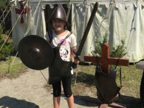 Girl dressed up as a solider in the Settlement Site at Roanoke Island Festival Park