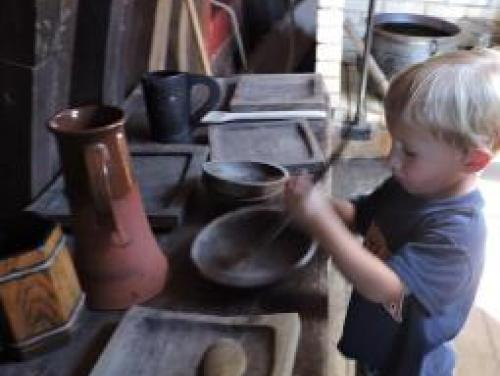Boy pretending to cook below deck on the Elizabeth II at Roanoke Island Festival Park