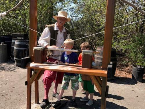 Historic interpreter teaching boy to use the bow lathe in the Settlement Site at Roanoke Island Festival Park