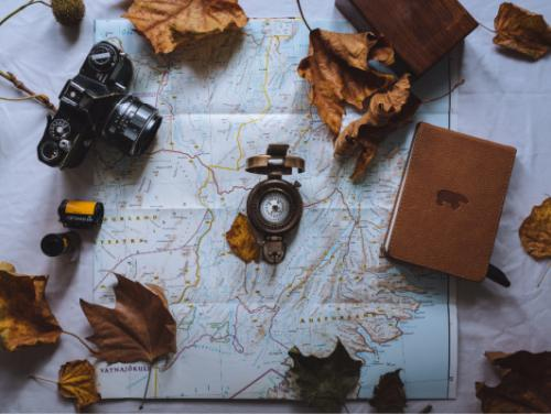 Map with leaves, camera, compass, and journal on top.
