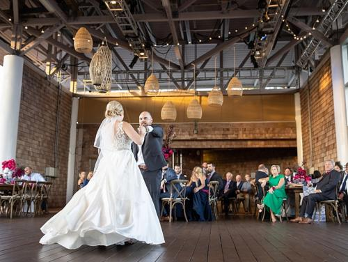 Groom dancing with bride on stage during wedding at Roanoke Island Festival Park